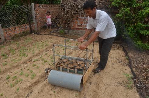 Ông Huỳnh Tiễn vận hành máy trỉa đậu phụng trong vườn nhà