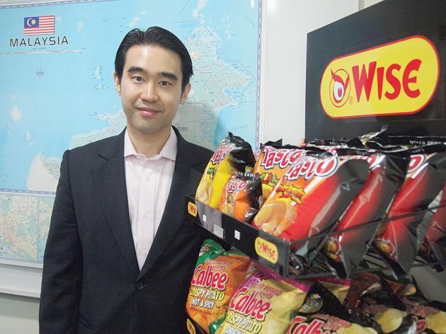 Ông Aswin Techajareonvikul chụp hình bên cạnh kệ trưng bày sản phẩm khoai tây chiên tại cửa hàng Jacy Foods (BJC), Malaysia.