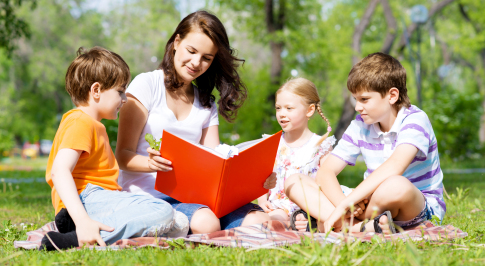 Kozzi-teacher-reads-a-book-to-children-in-a-summer-park-487-X-266